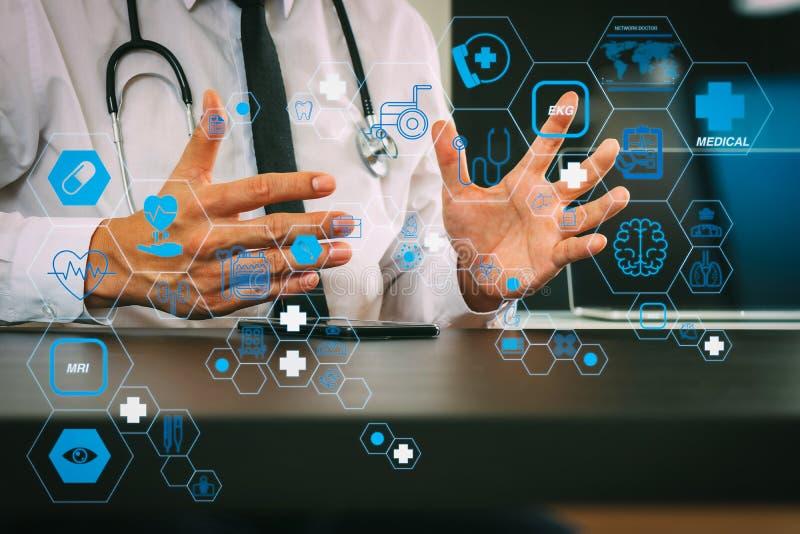 Médico inteligente que trabaja con un teléfono inteligente y un ordenador digital y un estetoscopio en un escritorio de madera en foto de archivo libre de regalías