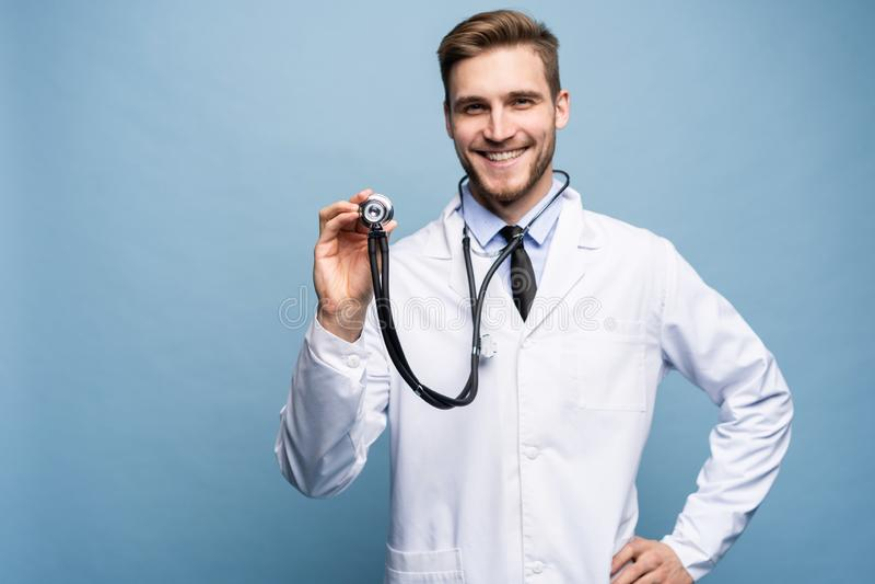 Médico joven hermoso que sostiene un estetoscopio, aislado sobre azul claro imágenes de archivo libres de regalías