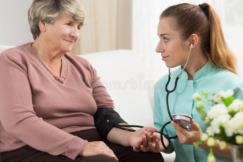 Médico joven que toma la presión arterial fotografía de archivo