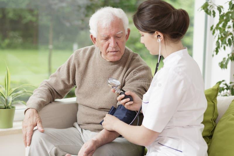 Médico joven que toma la presión arterial foto de archivo