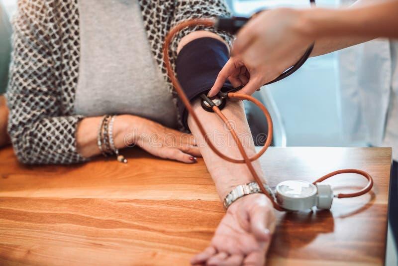 Médico joven que toma la presión arterial durante la visita casera, cl imágenes de archivo libres de regalías