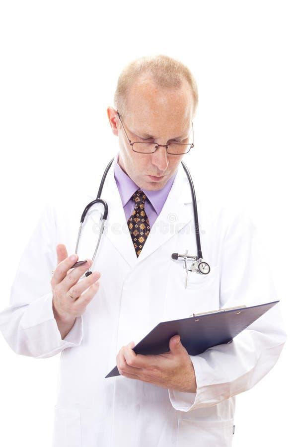 Médico médico que mira en el tablero foto de archivo