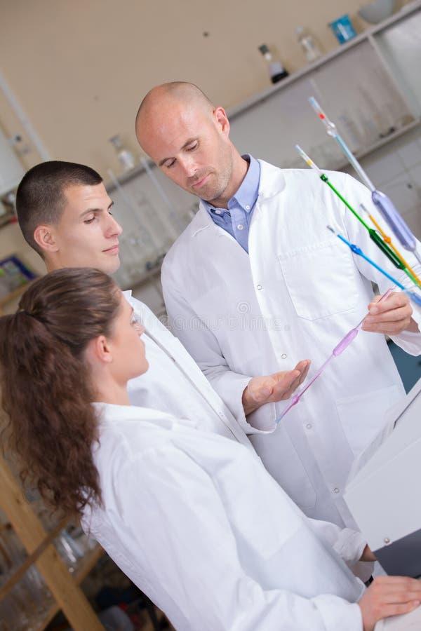 Médico masculino con los investigadores del laboratorio fotografía de archivo