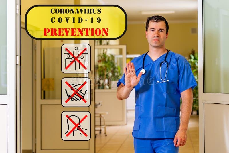 Médico masculino no corredor hospitalar, mostrando paragem com palma Ícones de prevenção do coronavírus fotografia de stock