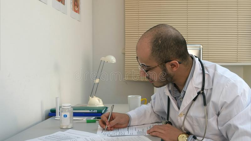 Médico masculino ocupado que trabalha com papéis e que tem a conversa telefônica em seu escritório imagem de stock royalty free