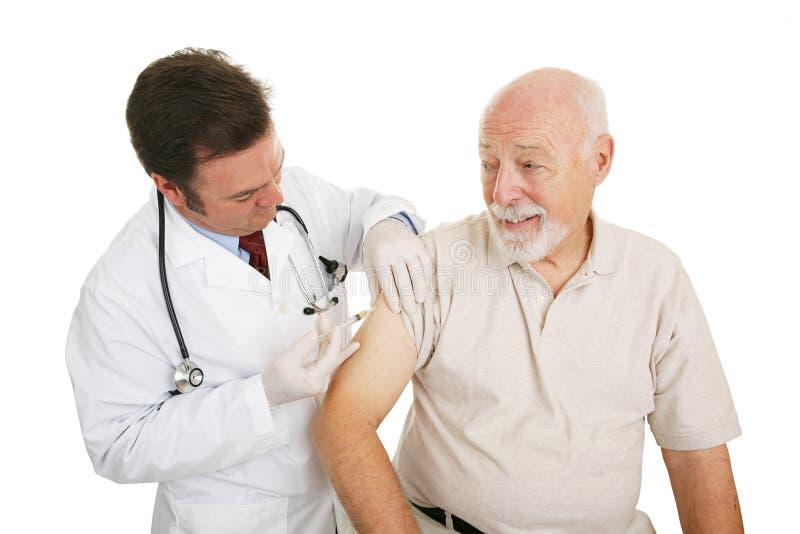 Médico mayor - vacuna contra la gripe fotos de archivo