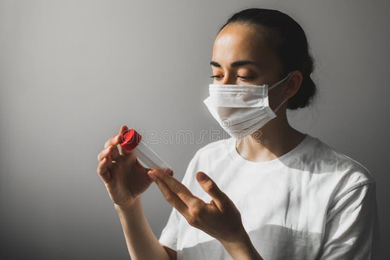 Médico na máscara médica com tubo de ensaio com coronavírus análise COVID- 19 imagem de stock