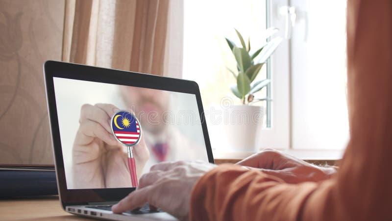 Médico na tela do computador e estetoscópio com bandeira da Malásia telemedicina malaia imagens de stock