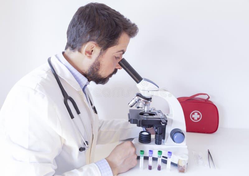 Médico olhando amostras ao microscópio em um laboratório Jovem cientista olhando pelo microscópio em um laboratório imagens de stock royalty free