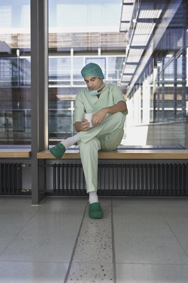 Médico pensativo With Coffee Cup en pasillo del hospital foto de archivo libre de regalías