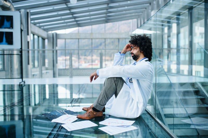 Médico preocupado y cansado sentado en el piso del hospital, concepto de virus de la corona foto de archivo