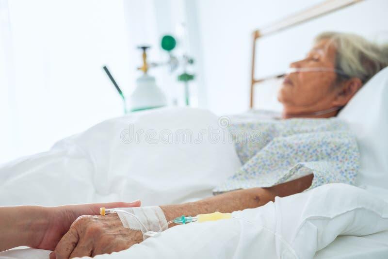 Médico que agujerea las manos pacientes mayores del ` s y que la conforta, imágenes de archivo libres de regalías