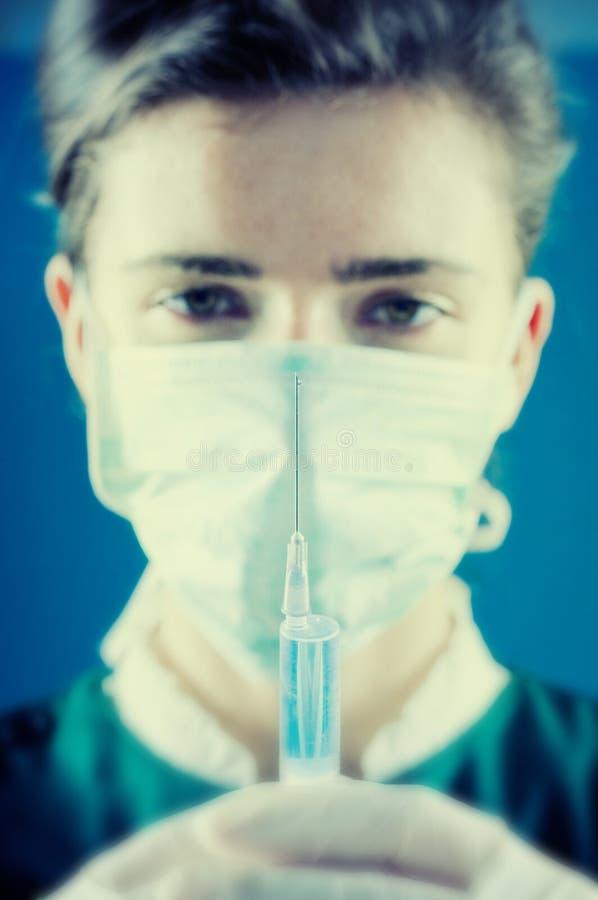 Médico que celebra una inyección en sus manos imagen de archivo