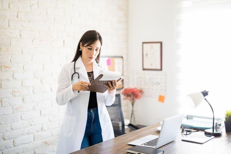 Médico que examina los informes del ` s del paciente imágenes de archivo libres de regalías
