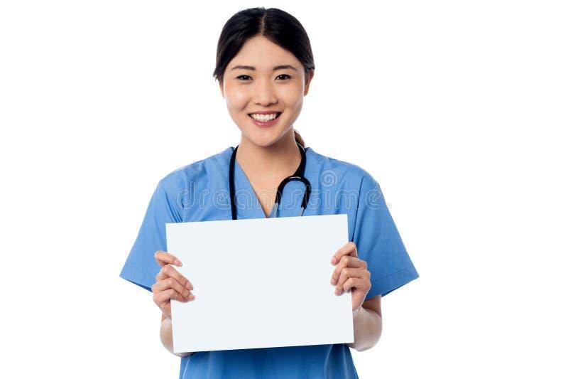 Médico que guardara a placa branca vazia do anúncio imagem de stock