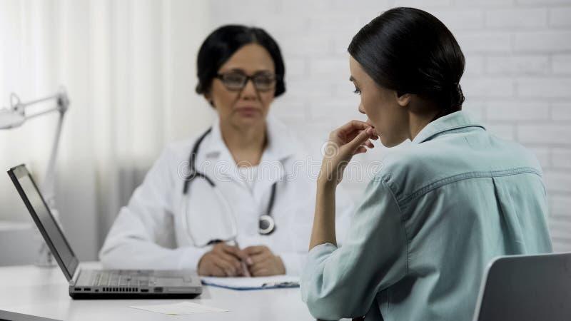 Médico que informa o paciente novo sobre o diagnóstico mau, doença incurável imagem de stock