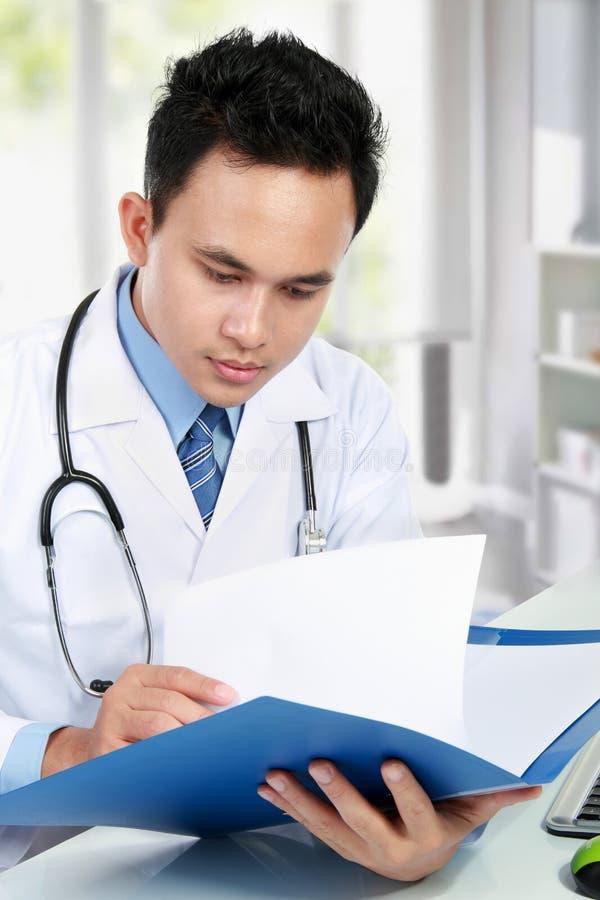 Médico que lee un informe imagen de archivo