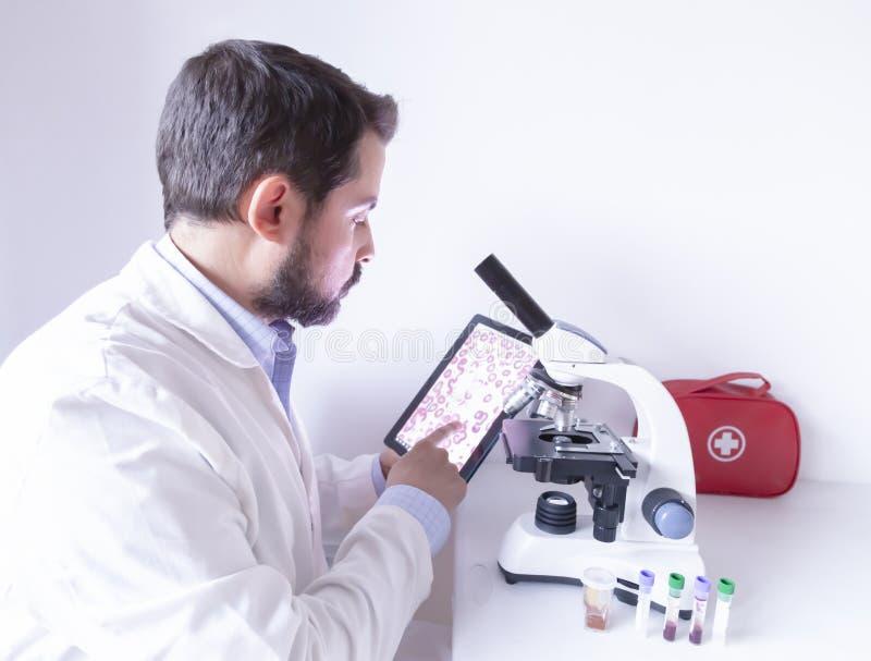 Médico que procura computador digital com comprimidos e trabalha no microscópio no laboratório hospitalar Conceito de pesquisa do fotografia de stock