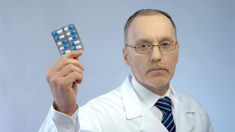 Médico serio que sostiene píldoras medicación eficaz disponible, de recomendación imagenes de archivo