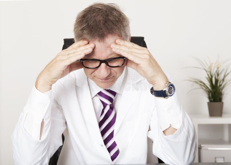 Médico Suffering Serious Headache imagens de stock