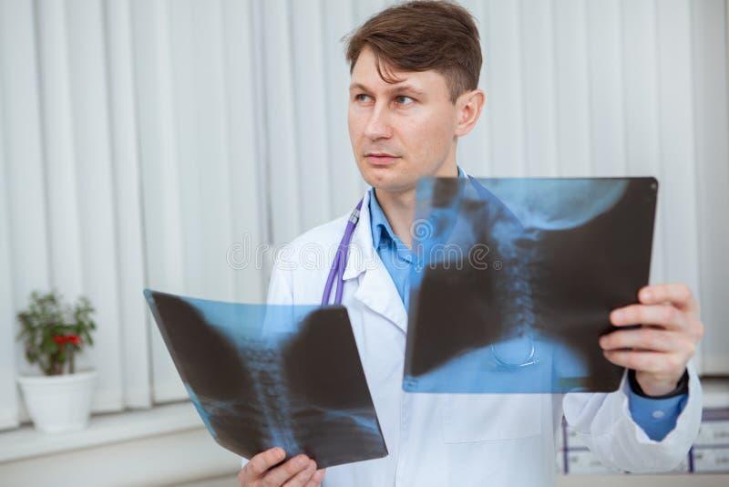 Médico varón maduro que examina los análisis de rayos X de un paciente foto de archivo