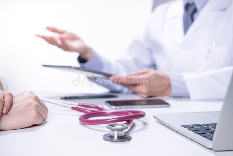 Médico y paciente que discuten y que consultan en sitio del examen del hospital fotografía de archivo libre de regalías