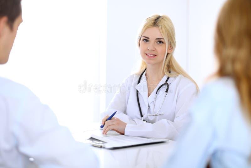 Médico y pacientes jovenes de los pares que discuten algo en la tabla Da el primer fotografía de archivo libre de regalías