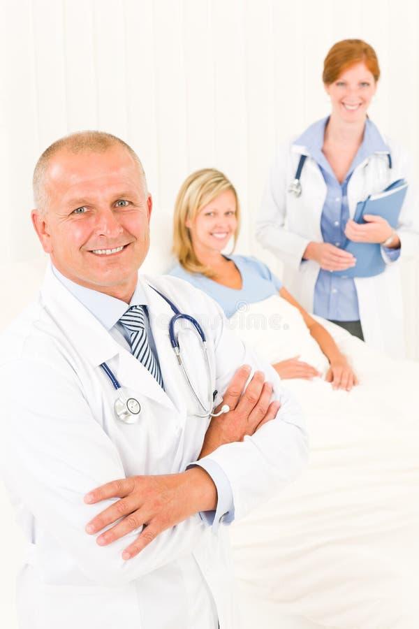 Médicos com a cama de encontro do paciente hospitalizado imagens de stock