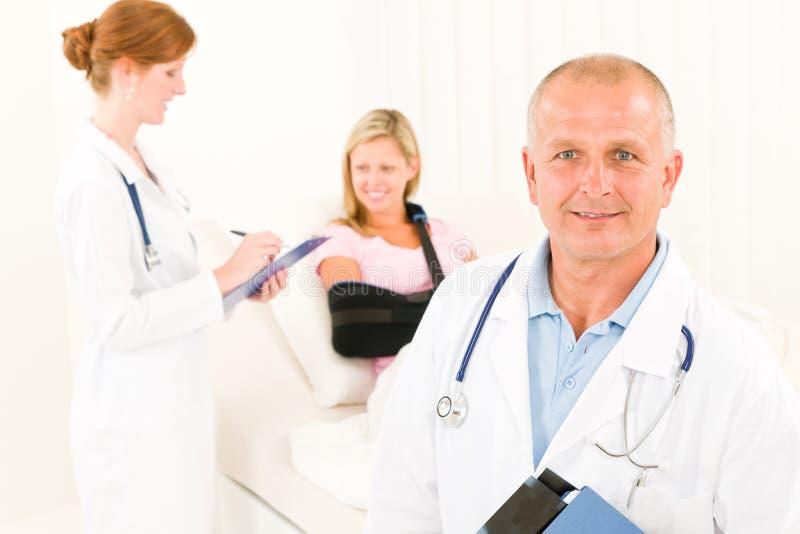Médicos com a cama de encontro do paciente hospitalizado fotografia de stock royalty free