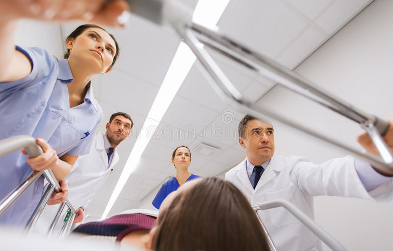 Médicos com a mulher na marquesa do hospital na emergência imagem de stock royalty free