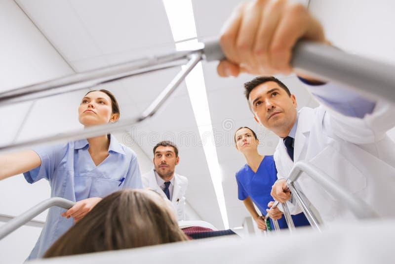 Médicos com a mulher na marquesa do hospital na emergência imagens de stock