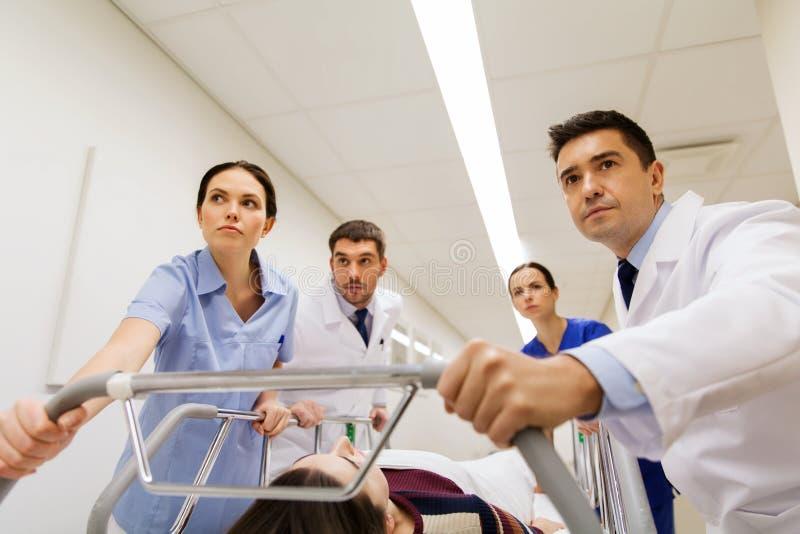 Médicos com a mulher na marquesa do hospital na emergência imagem de stock
