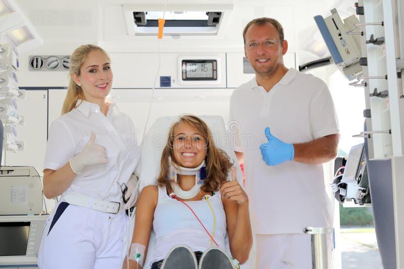 Médicos com paciente em um carro da ambulância feliz com polegares acima fotografia de stock