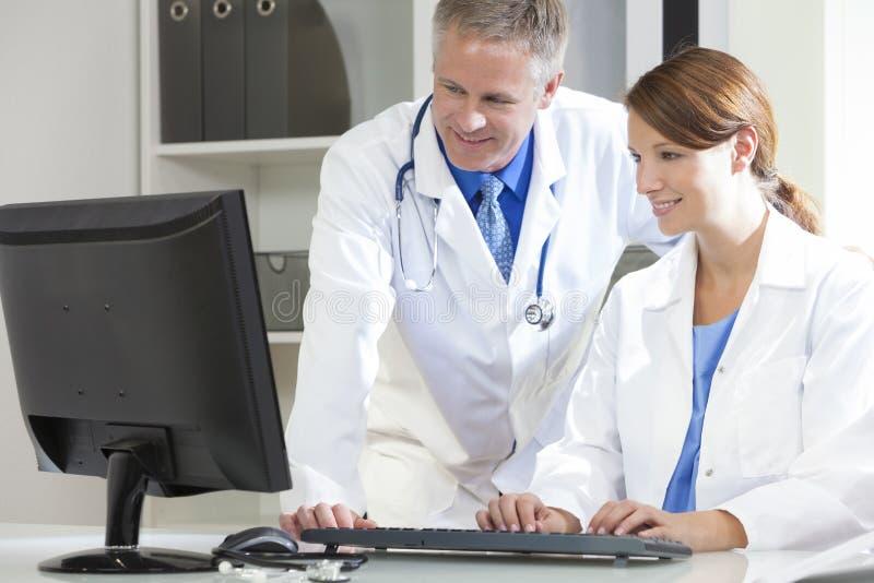 Médicos de hospital hembra-varón que usan el ordenador fotos de archivo libres de regalías