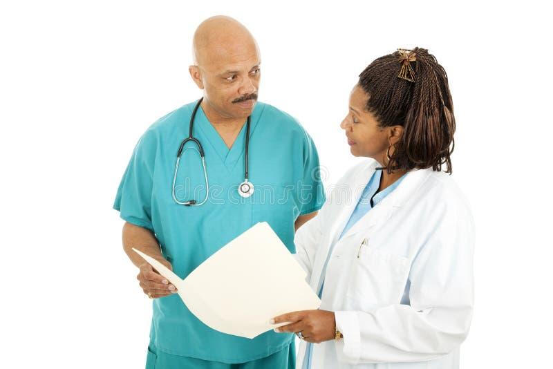 Médicos que leen la carta fotografía de archivo