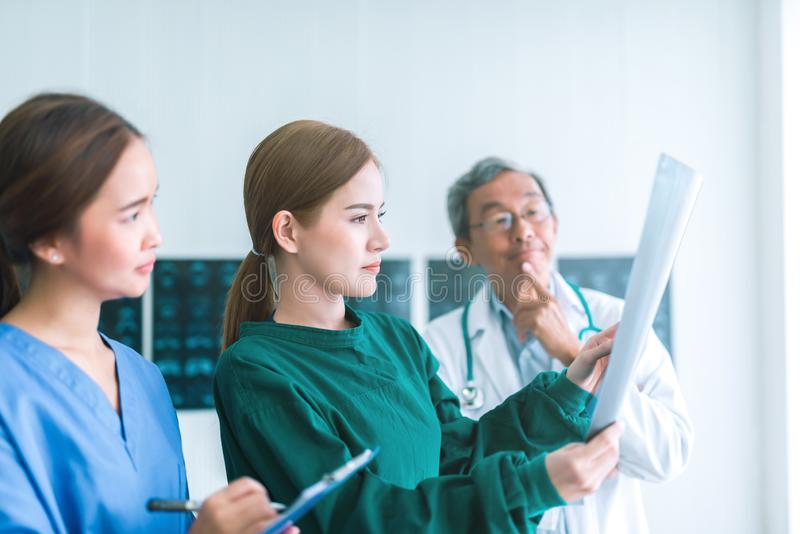 Médicos que miran radiografías en un hospital comprobación de la película del rayo del pecho x en la sala con la enfermera y el d imagenes de archivo