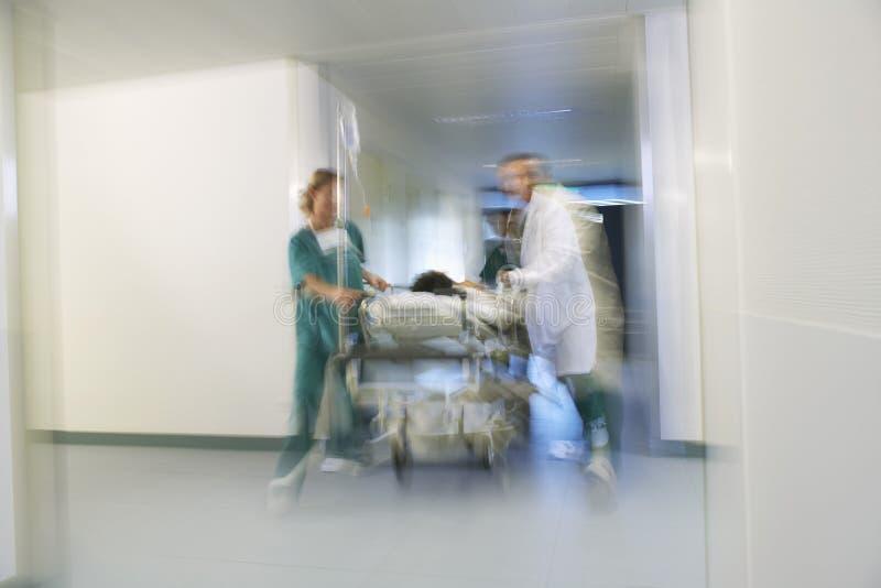 Médicos que mueven al paciente en la camilla a través del pasillo del hospital fotografía de archivo