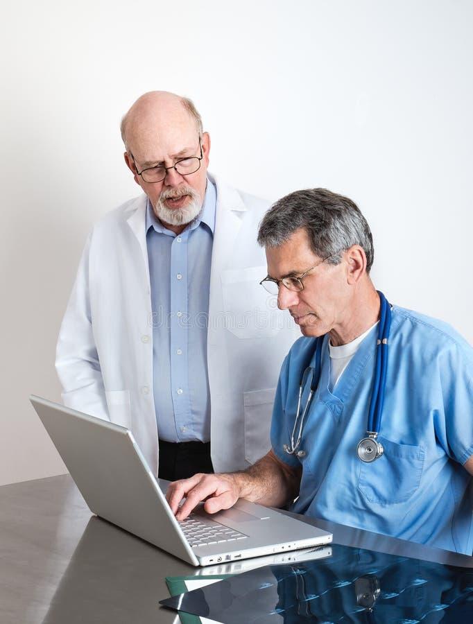Médicos superiores que discutem varreduras do filme do MRI do paciente fotos de stock