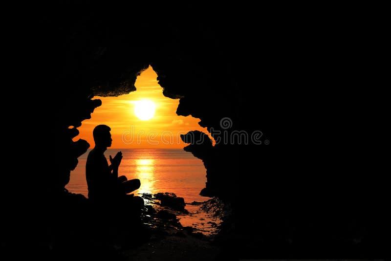 Méditation d'homme et prière dans la caverne par la plage au coucher du soleil image stock