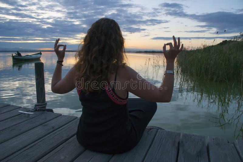 Méditation de pratique de femme en position de yoga de lotus sur une jetée en bois photo stock
