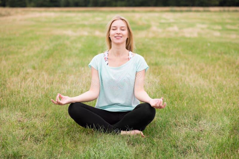 Méditation sur le pré image stock
