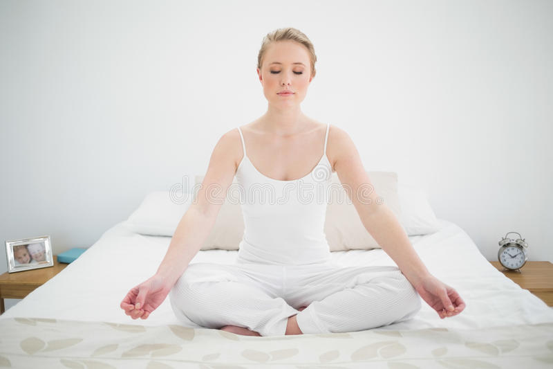 Méditer assez blond naturel sur le lit avec les yeux fermés photos stock