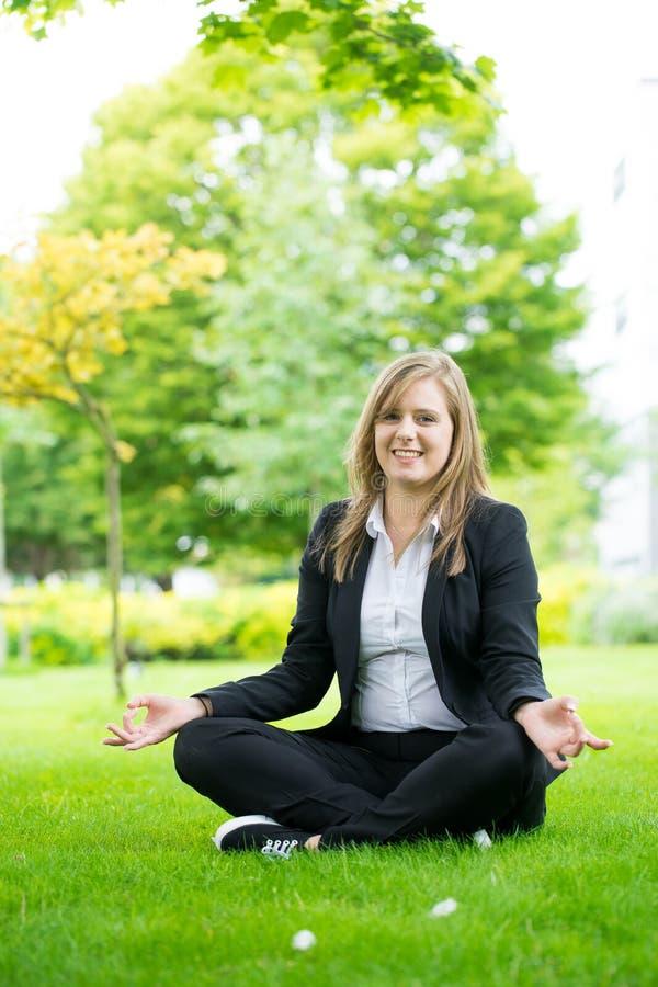 Méditer et yoga de femme d'affaires en parc photographie stock libre de droits
