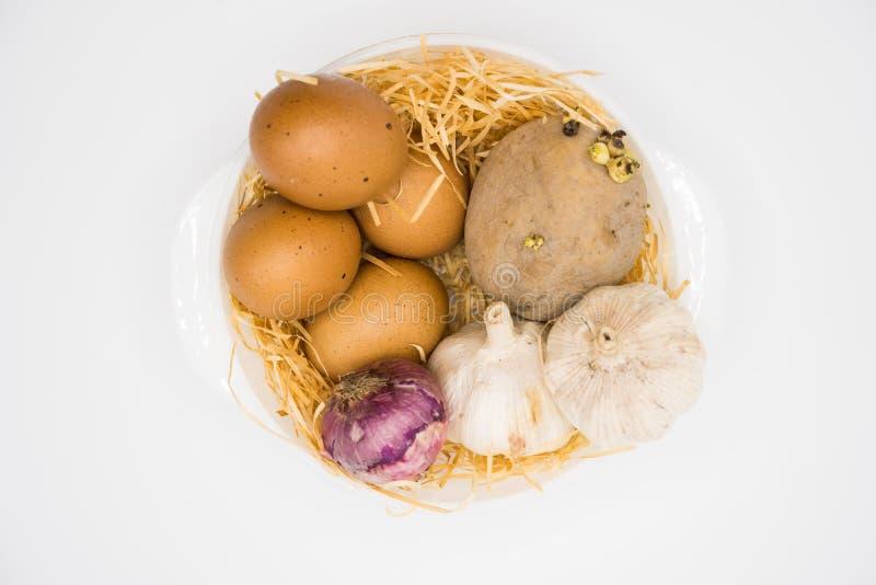 Mélange d'oignon et d'ail de pomme de terre d'oeufs sur le nid avec le fond blanc photographie stock