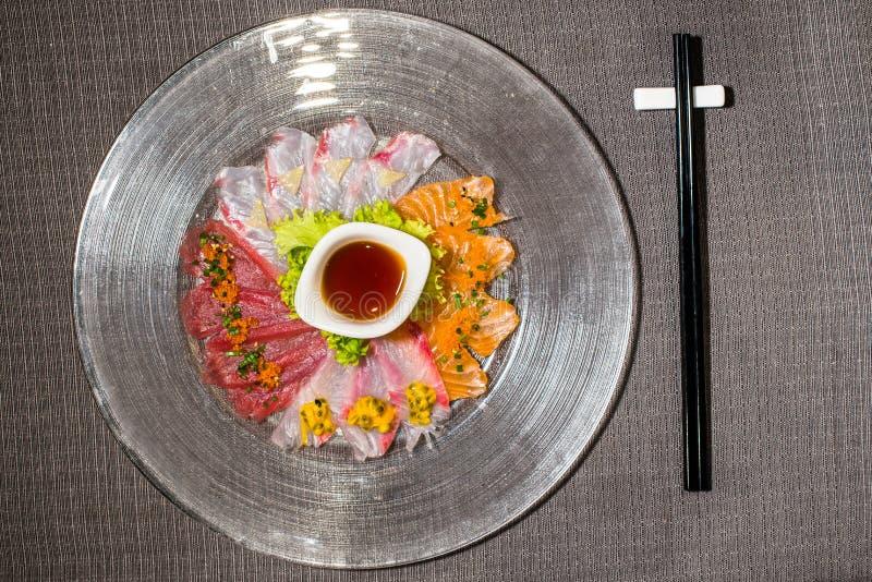 Mélange de carpaccio différent de poissons avec de la salade et la sauce à agrumes photographie stock