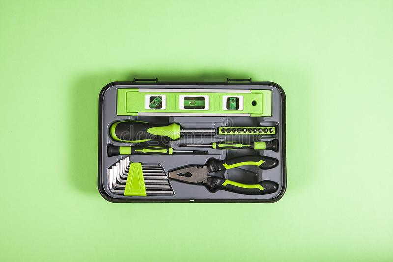 Mélange de différents outils dans une boîte sur le fond vert photos stock