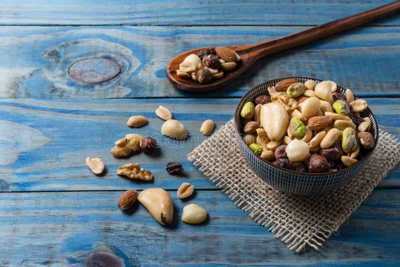 Mélange des écrous et des pistaches à l'intérieur du pot en céramique au-dessus du bois de pin bleu images libres de droits