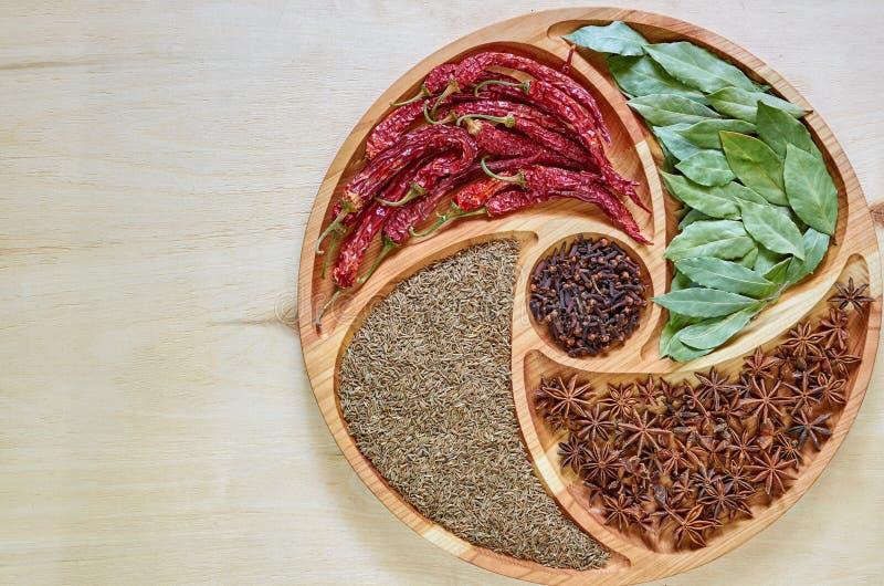 Mélange des épices chaudes du plat en bois : anis d'étoile, feuilles de baie, paprika, clous de girofle secs et haut étroit de cu photos stock
