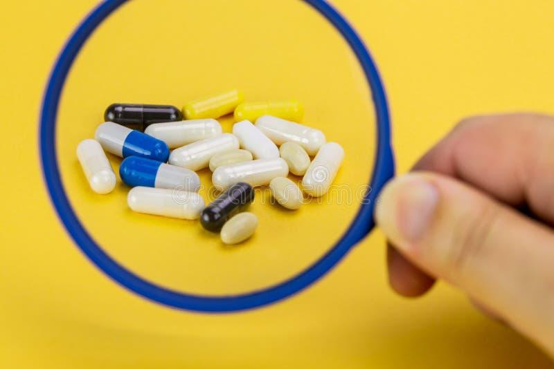 Mélange des pilules sur un fond jaune magnifié par une loupe image stock
