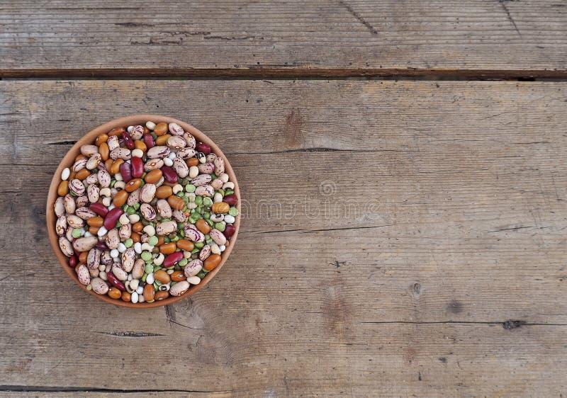Mélange des variétés de haricots, d'azuki et des lentilles vertes dans une cuvette sur une planche en bois superficielle par les  images stock